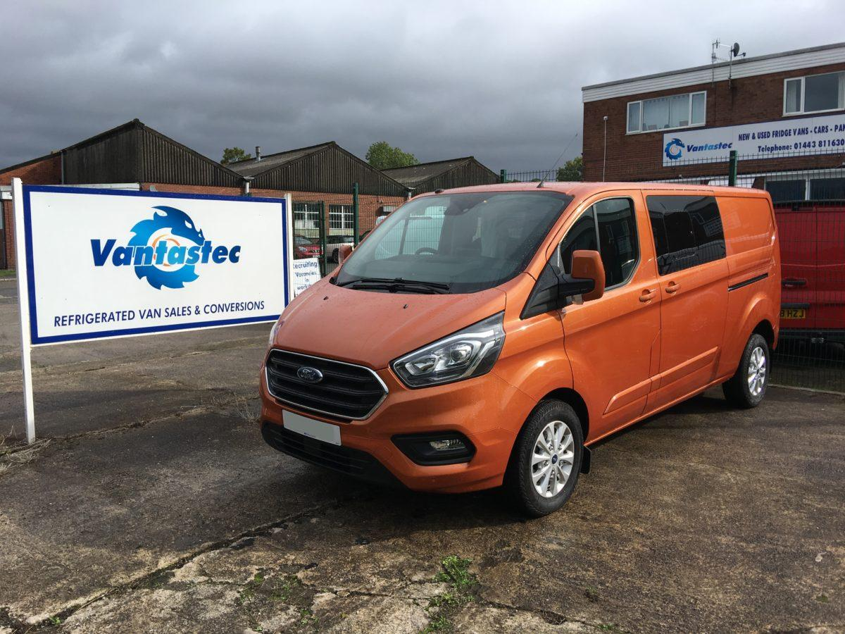 3/4 Front view of orange Ford Transit Custom crew van